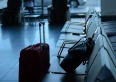 ingepakte rolkoffer op vliegveld